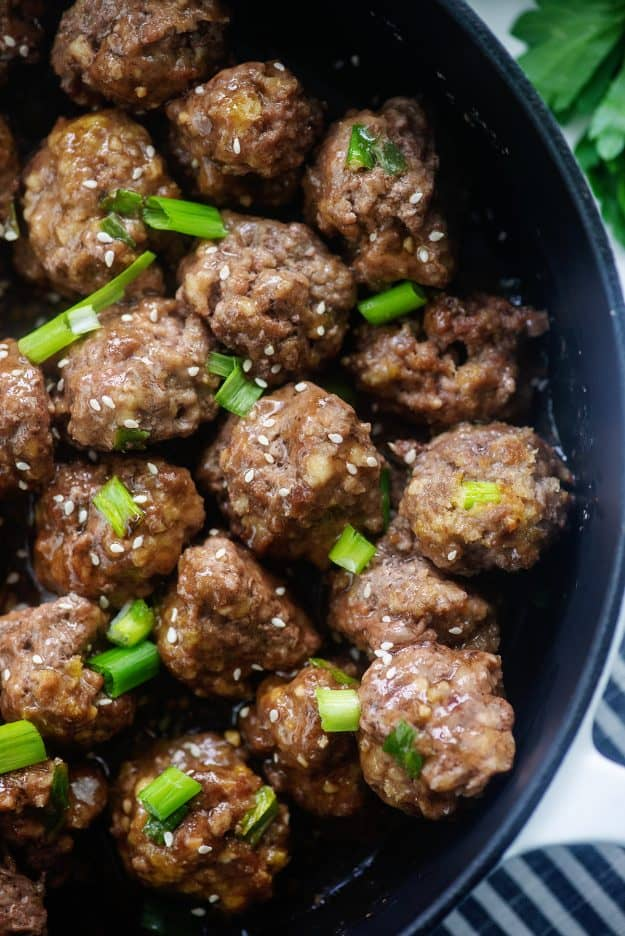 overhead view of meatballs in teriyaki sauce in black dish.