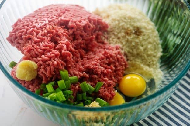 ingredients for teriyaki meatballs in glass mixing bowl.