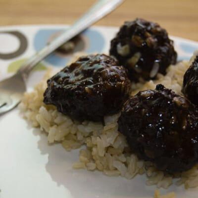 A close up of teryaki meatballs on rice