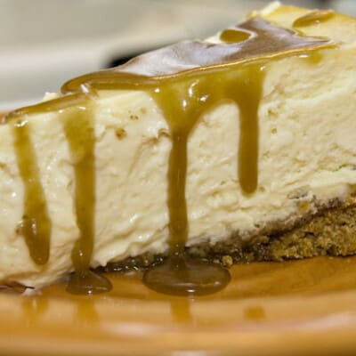 A close up of cheesecake topped with whisky butter sauce