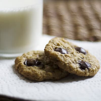 Two oatmeal cookies on a paper napkin in front of a glass of milk.