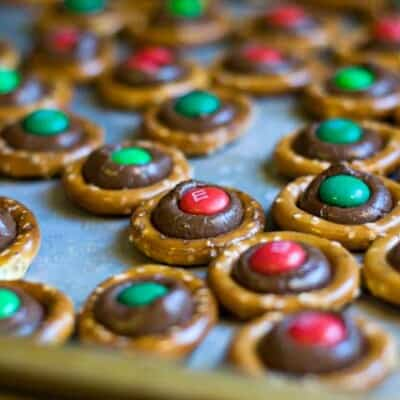 A bunch of pretzel rings with melted chocolate and m&m's on a baking sheet.