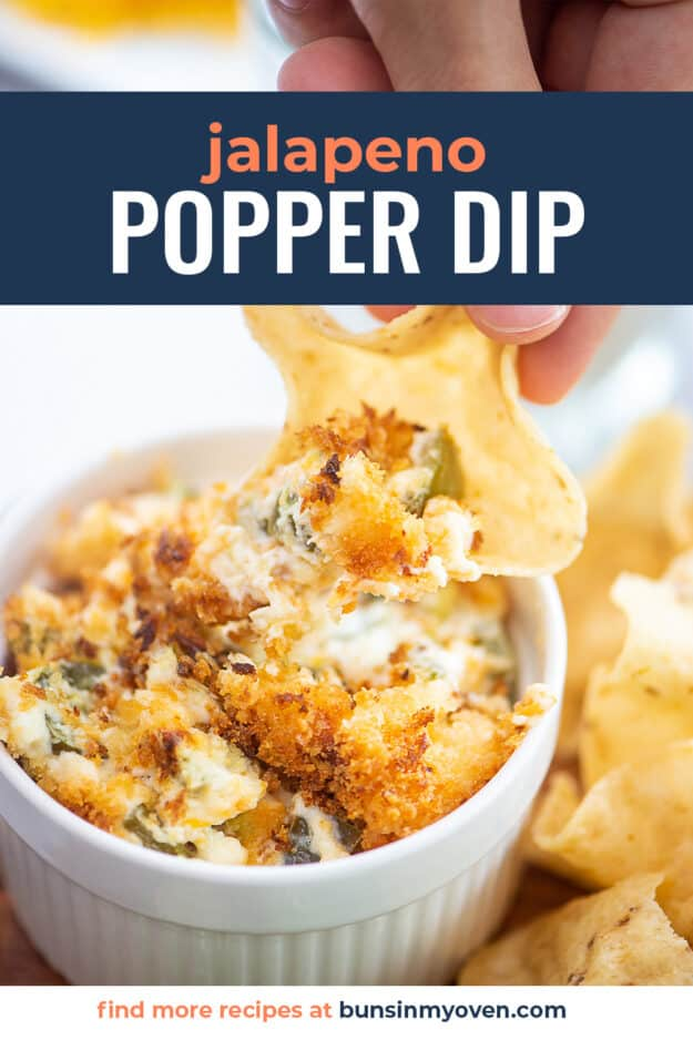 hand dipping a chip into dip.