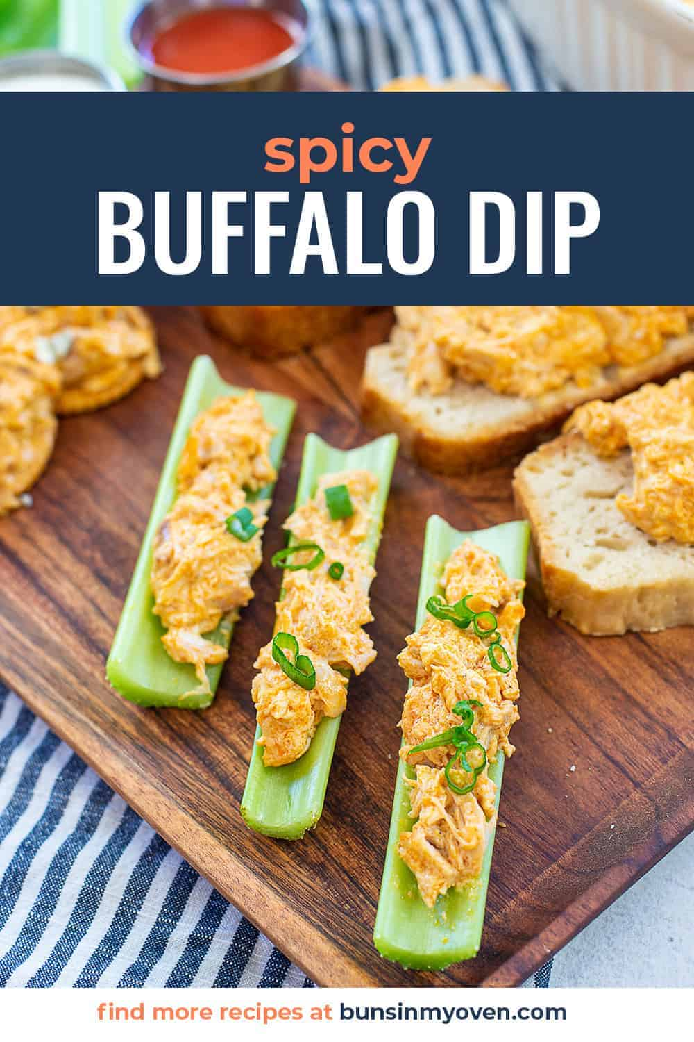 celery filled with buffalo chicken dip on wooden board.