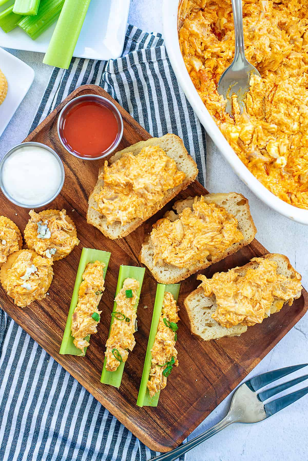 overhead view of buffalo chicken dip on celery and bread.