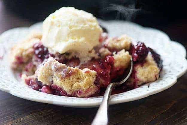 Berry cobbler on white plate with ice cream