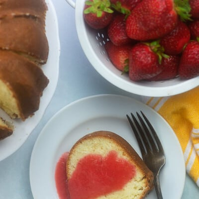 Plate of pound cake next to a bowl of strawberries.