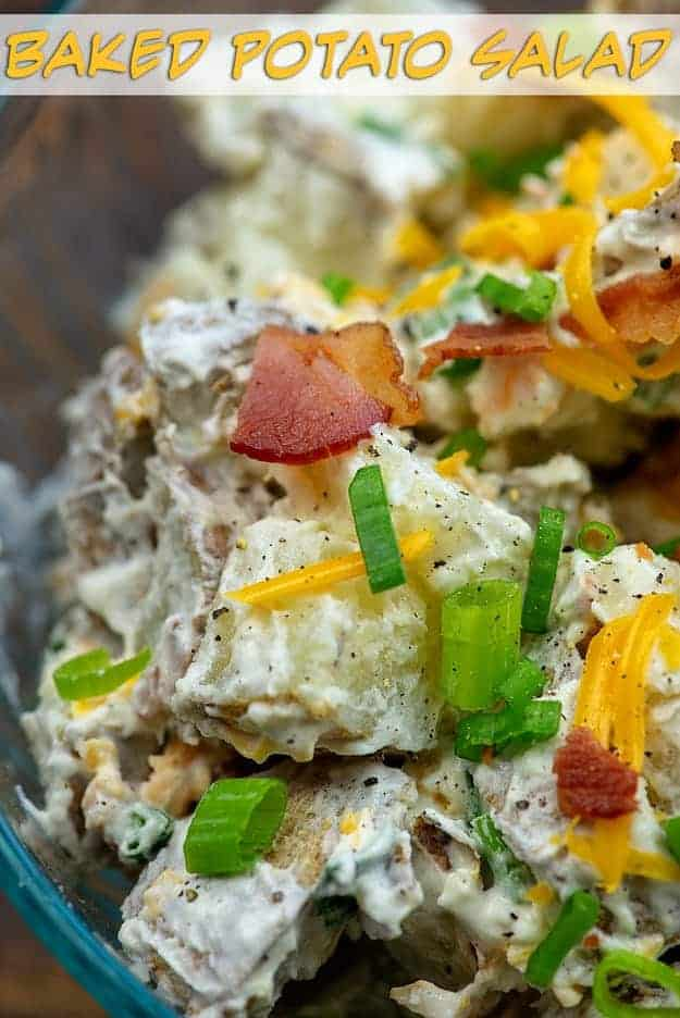 A closeup of bacon and green onions on top of potato salad.