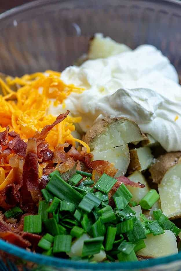 ingredients for loaded potato salad in glass bowl.