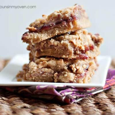 A stack of peanut butter and jelly bars on a square plate