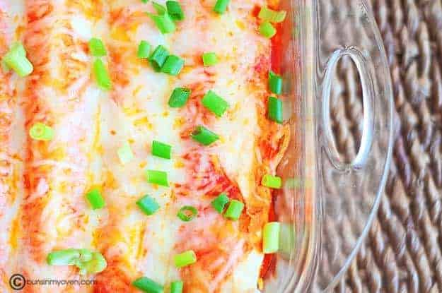 A clear glass baking pan with enchilada casserole in it.