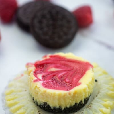 cheesecake on muffin liner with oreos and raspberries
