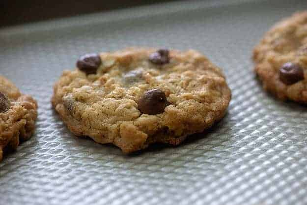 A cooked chocolate chip cookie on a baking sheet