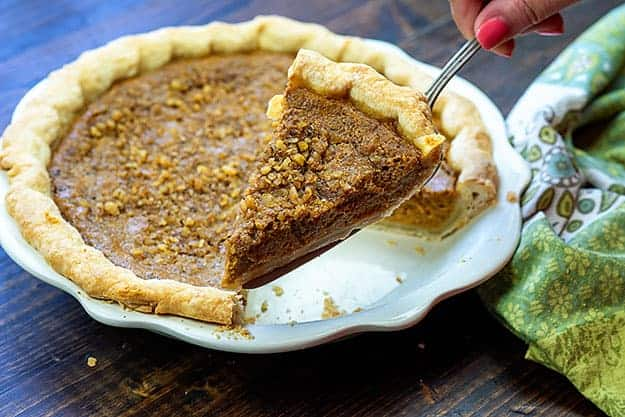 A piece of pumpkin pie being held up to the camera on a pie scoop.