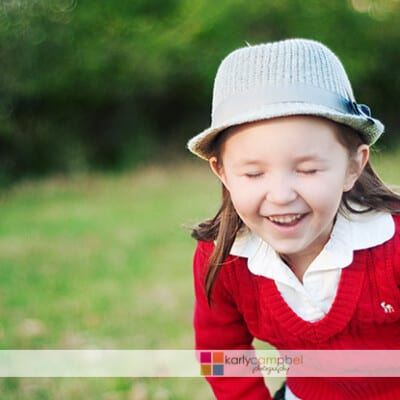 A little girl wearing a hat and laughing