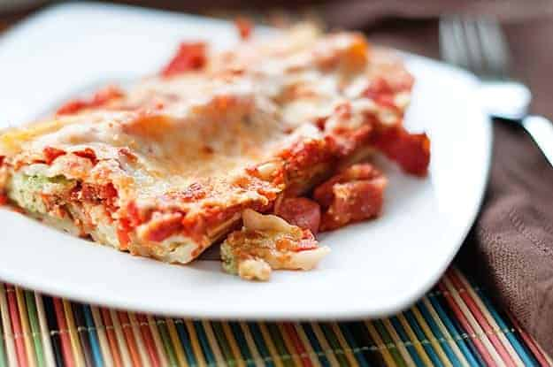 Close up of manicotti on a square white plate.