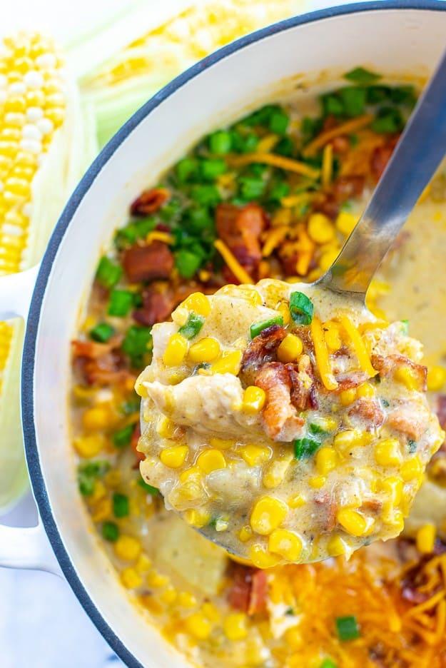 corn chicken chowder on ladle in bowl.