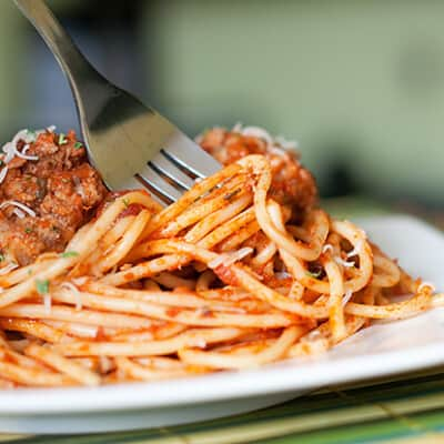 A closeup of a plate of spaghetti with a fork in it