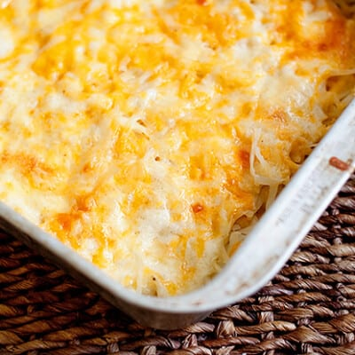 Melted cheese and shredded potatoes in a white baking dish.