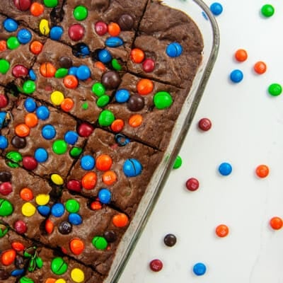 brownies topped with m&m's in glass baking dish.