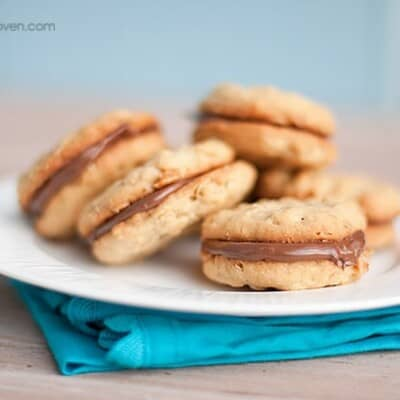 A plate of sandwich cookies on a folded blue napkin.
