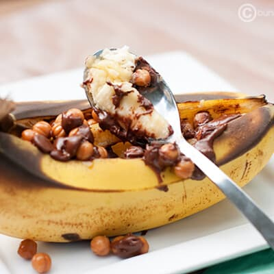 Grilled bananas topped with chocolate syrup.