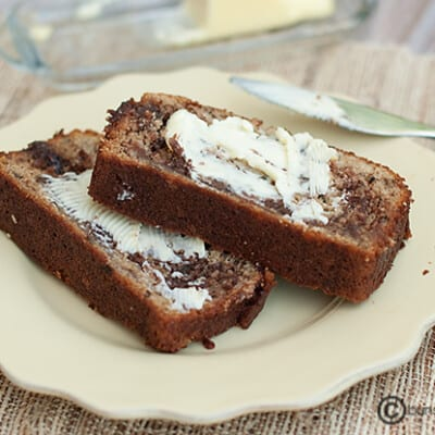 A piece of banana bread with a butter spread.
