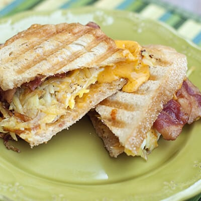 A bacon and egg panini on a decorative plate