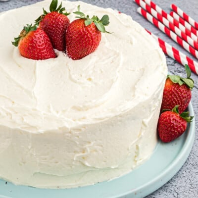 white frosting with berries on layer cake.