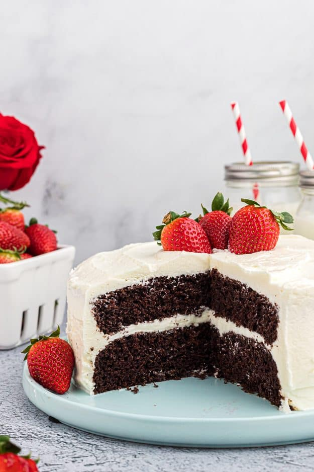 chocolate cake on cake plate with whipped frosting and berries.