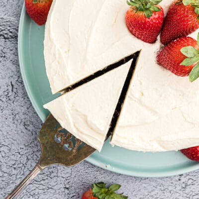 cut cake topped with whipped frosting and strawberries.