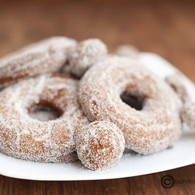 A close up of a few apple cider donuts on a plate.