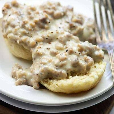 small white plate with a biscuit topped with sausage gravy.
