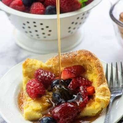 german pancake with fresh fruit and syrup on white plate