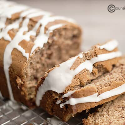 A loaf of maple cinnamon quick bread partially sliced on a cooling rack.