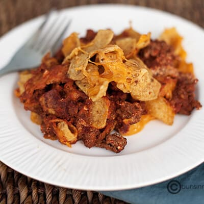 A close up of a Frito pie serving on a small white plate.