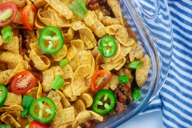 Frito chili pie in casserole dish topped with jalapenos and tomatoes.