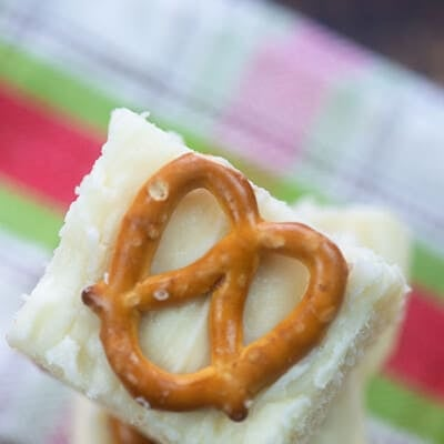A close up of white fudge with a mini pretzel on it.