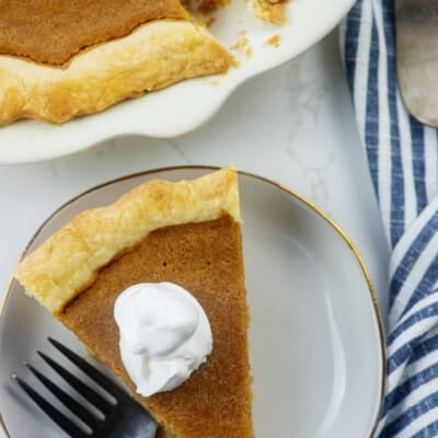 sweet potato pie on white plate with whipped cream.