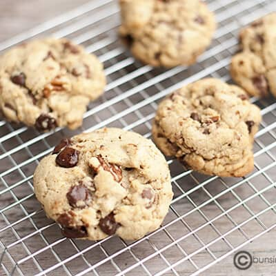 Five brown butter chocolate chip cookies on a wire cooling rack.