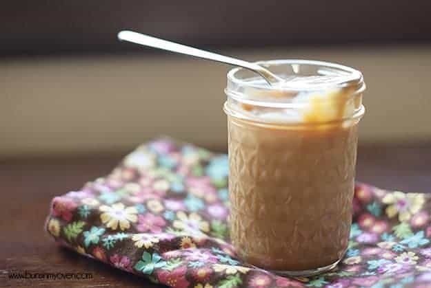 Dulce de leche in a glass jar with a spoon in it.