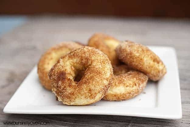 Baked cake donuts with cinnamon and sugar on a square white plate.