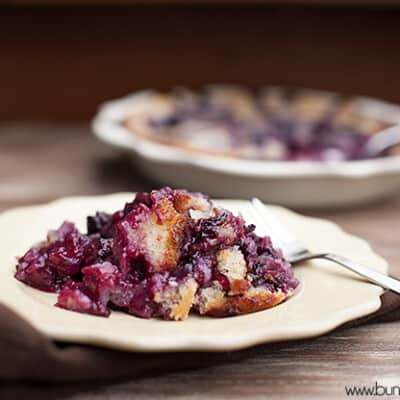 A serving of blackberry cobbler on a white plate in front of a cobbler pie.