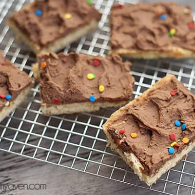 Sugar cookie bars with chocolate icing on a cooling rack