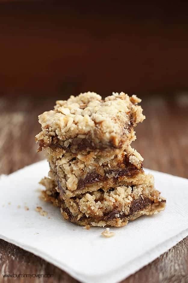 stacked oatmeal carmelitas on a wooden table.