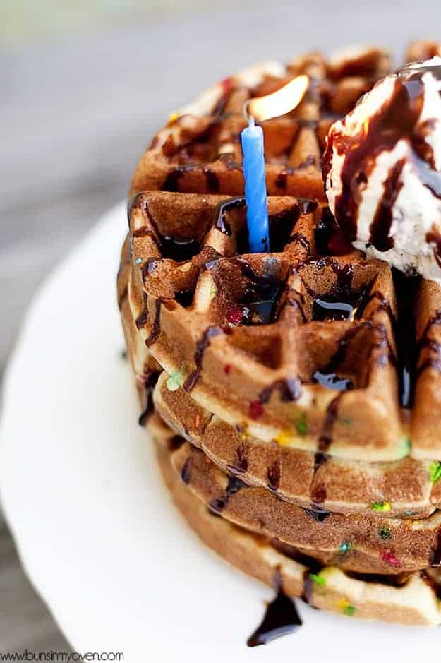 A closeup of a confetti waffle with a birthday candle in it