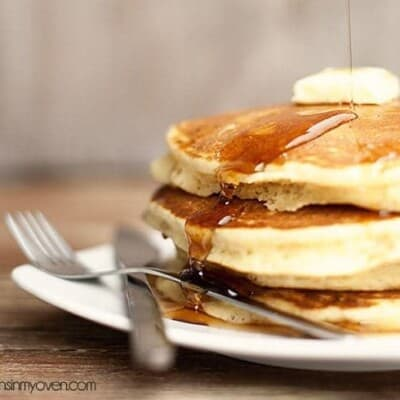 The stack of pancakes with syrup drizzled over the top