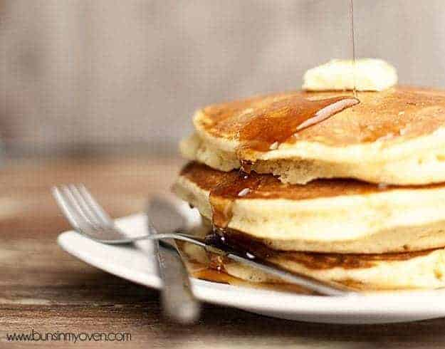 A side view of syrup being poured on top of a stack of pancakes