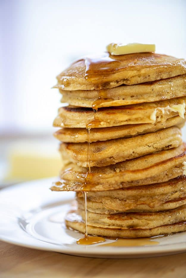 huge stack of fluffy buttermilk pancakes with syrup.
