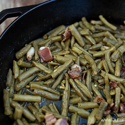 A closeup of green beans and bacon cooking in a cast iron skillet